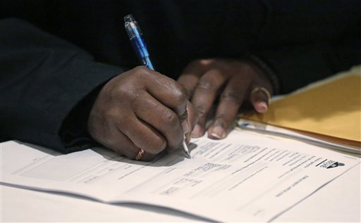 FILE - In this April 22, 2015, file photo, a job seeker fills out an application during a National Career Fairs job fair in Chicago. The Labor Department said Thursday, Jan. 14, 2016, applications for jobless aid rose 4,000 to a seasonally adjusted 284,000. (AP Photo/M. Spencer Green, File)