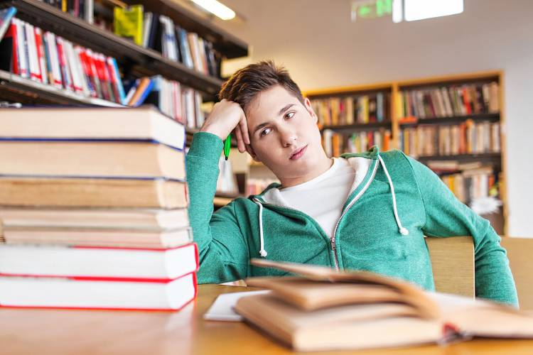 people%2C+knowledge%2C+education%2C+literature+and+school+concept+-+bored+student+or+young+man+with+books+dreaming+in+library