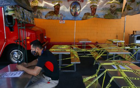 FILE - In this July 1, 2020, file photo, Abel Gomez waits for his order at Mariscos Linda food truck as dining tables are sealed off with caution tape due to the coronavirus pandemic in Los Angeles. Gov. Gavin Newsom announced a new, color-coded process Friday, Aug. 28, 2020, for reopening California businesses amid the coronovirus pandemic that is more gradual than the state's current rules to guard against loosening restrictions too soon. Counties will move through the new, four-tier system based on their number of cases and percentage of positive tests. It will rely on those two metrics to determine a tier: case rates and the percentage of positive tests. (AP Photo/Jae C. Hong, File)