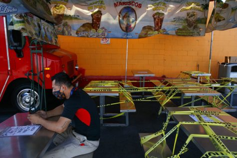 FILE - In this July 1, 2020, file photo, Abel Gomez waits for his order at Mariscos Linda food truck as dining tables are sealed off with caution tape due to the coronavirus pandemic in Los Angeles. Gov. Gavin Newsom announced a new, color-coded process Friday, Aug. 28, 2020, for reopening California businesses amid the coronovirus pandemic that is more gradual than the state