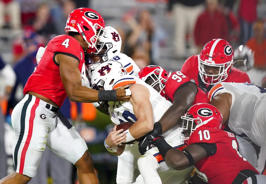 Georgia's Jordan Davis (99), Nolan Smith (4) and Malik Herring (10) tackle Auburn quarterback Bo Nix (10) during the first half of an NCAA college football game Saturday, Oct. 3, 2020, in Athens, Ga. (AP Photo/Brynn Anderson)