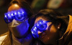Guatemalan tourists Alejandra Paiz, left, and Argelia Gordillo wear festive glasses as the pair and their sons mark New Years Eve at the Angel of Independence monument in Mexico City, just after midnight on Friday, Jan. 1, 2021. Although Mexico City cancelled its annual New Years celebration to curb the spread of the COVID-19 pandemic, dozens of people came out in small groups to mark midnight with selfies and video calls from the iconic city landmark.(AP Photo/Rebecca Blackwell)