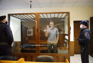 Opposition leader Alexei Navalny stands in a cage in the Babuskinsky District Court in Moscow, Russia, Saturday, Feb. 20, 2021. Two trials against Navalny are being held Moscow City Court one considering an appeal against his imprisonment in the embezzlement case and another announcing a verdict in the defamation case. (AP Photo/Alexander Zemlianichenko)