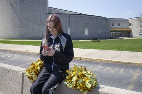 In this photo provided by the American Civil Liberties Union, Brandi Levy wears her former cheerleading outfit as she looks at her mobile phone while sitting outside Mahanoy Area High School in Mahanoy City, Pa., on April 4, 2021. A profanity-laced posting by Levy on Snapchat has ended up before the Supreme Court in the most significant case on student speech in more than 50 years. At issue in arguments to be heard Wednesday, April 28, 2021, via telephone, is whether public schools can discipline students over something they say off-campus. (Danna Singer/ACLU via AP)